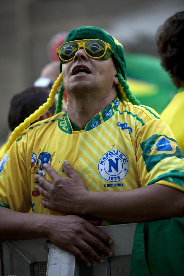 A fan sings the Brazilian national anthem prior to the start of the World Cup group A soccer match between Brazil and Mexico, at the FIFA Fan Fest in Sao Paulo, Brazil, Tuesday, June 17, 2014. (AP Photo/Dario Lopez-Mills)
