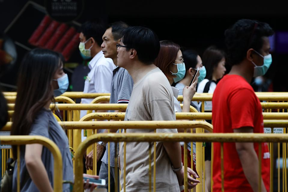 SINGAPORE - MARCH 28:  Shoppers wearing protective mask queue to enter a shopping mall with a social distancing markers in place on March 28, 2020 in Singapore.  Singapore government introduced a supplementary budget on March 26 with measures worth S$48 billion to support Singaporeans and businesses to cope with the Covid-19 pandemic.  (Photo by Suhaimi Abdullah/Getty Images)