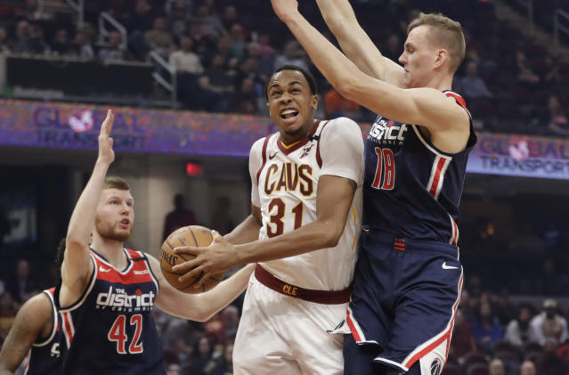 Cleveland Cavaliers' John Henson (31) drives between Washington Wizards' Davis Bertans (42) and Anzejs Pasecniks (18) in the first half of an NBA basketball game, Thursday, Jan. 23, 2020, in Cleveland. (AP Photo/Tony Dejak)