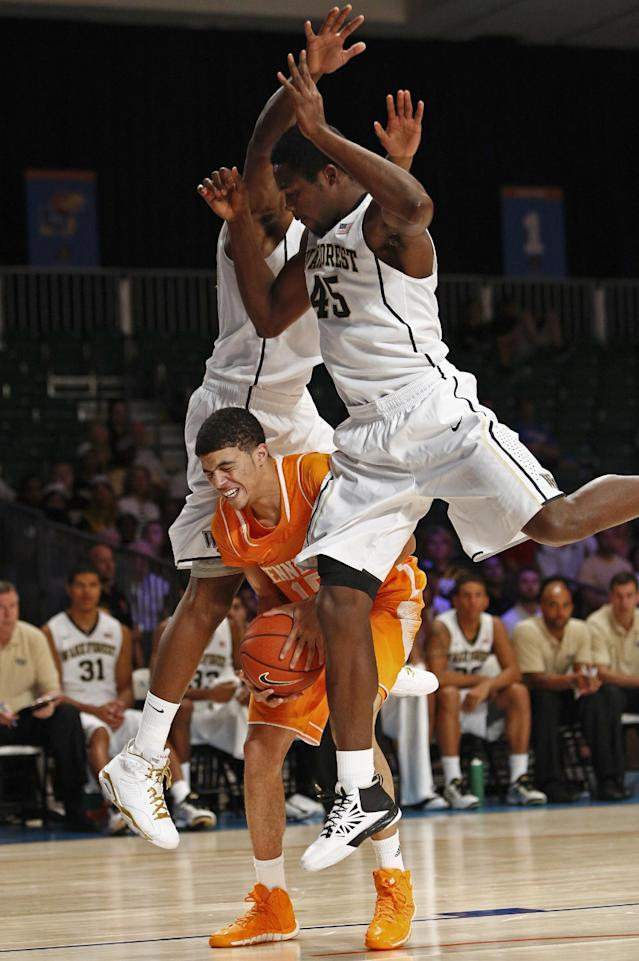 Tennessee's Darius Thompson, center, is sandwiched by Wake Forest's Arnaud William Adala Moto, right, and Travis McKie during the first half of an NCAA college basketball game in Paradise Island, Bahamas, Saturday, Nov. 30, 2013. (AP Photo/Bahamas Visual Services, Tim Aylen)