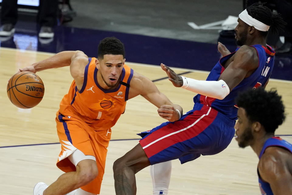 Phoenix Suns guard Devin Booker (1) fouls Detroit Pistons forward Jerami Grant during the second half of an NBA basketball game, Friday, Feb. 5, 2021, in Phoenix. (AP Photo/Matt York)