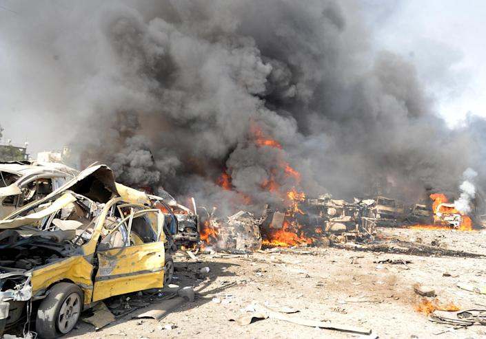 In this photo released by the Syrian official news agency SANA, flames and smoke raise from burning cars after two bombs exploded, at Qazaz neighborhood in Damascus, Syria, on Thursday May 10, 2012. Two large explosions ripped through the Syrian capital Thursday, heavily damaging a military intelligence building and leaving blood and human remains in the streets. (AP Photo/SANA)