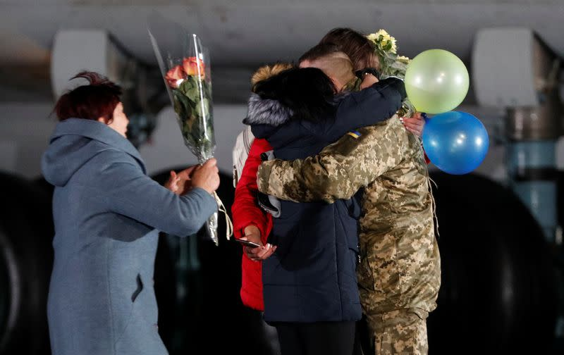 Relatives embrace a Ukrainian serviceman exchanged during a prisoners of war swap at an airport outside Kiev
