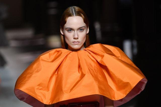 Givenchy models sported glossy lips, dewy skin and sleek hair, parted at the center, for a high-fashion aesthetic