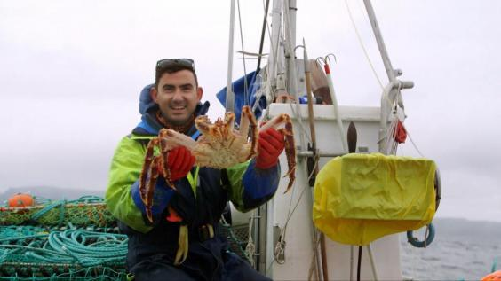 Simon Parker holding a king crab – their leg span can grow to 6ft