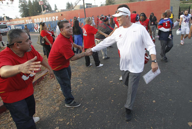 Fresno State coach Jeff Tedford gets congratulated after the game against Boise State during the second half of an NCAA college football game in Fresno, Calif., Saturday, Nov. 25, 2017. Fresno State won 28-17. (AP Photo/Gary Kazanjian)