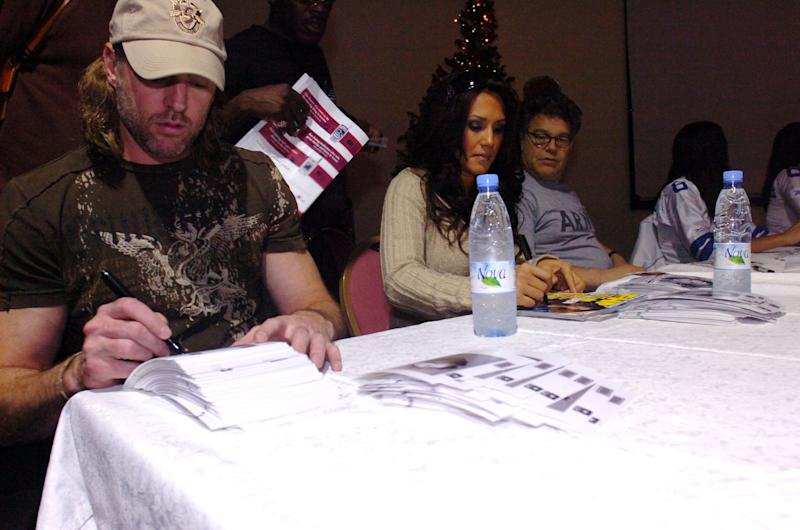 From left to right, musician Darryl Worley, sportscaster Leeann Tweeden and comedian Al Franken greet soldiers during an autograph session in Kuwait, Dec. 14, 2006.