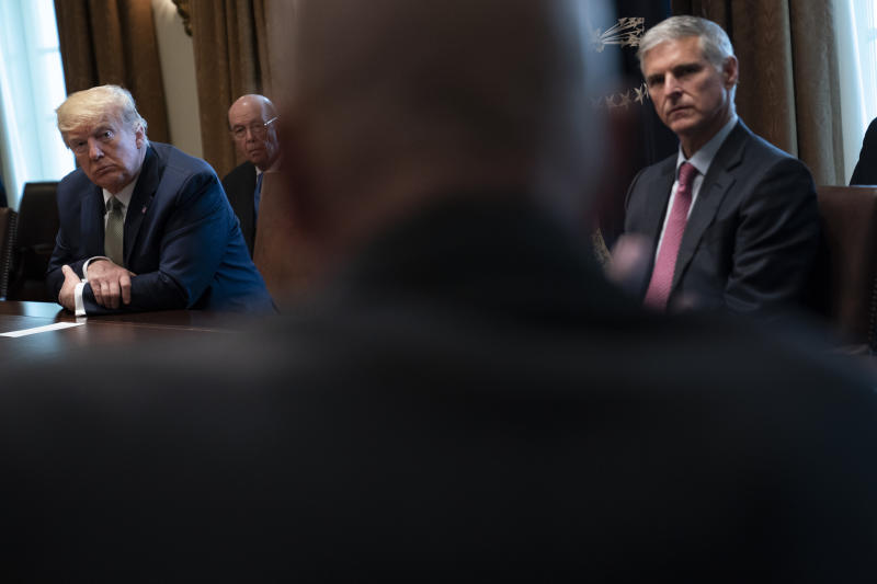 President Donald Trump, left, and Christopher Nassetta, President & CEO of Hilton, listen during a meeting with tourism industry executives about the coronavirus, in the Cabinet Room of the White House, Tuesday, March 17, 2020, in Washington. (AP Photo/Evan Vucci)