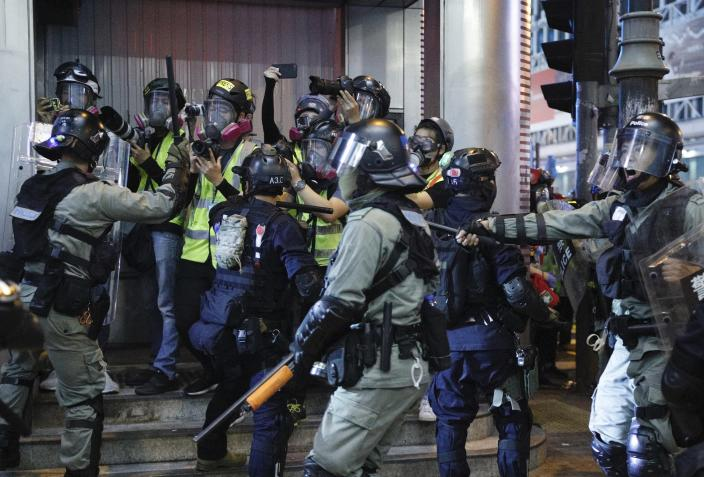 """Hong Kong police officers push back journalists during a rally in Hong Kong on Sunday, Oct. 27, 2019. Hong Kong police fired tear gas Sunday to disperse a rally called over concerns about police conduct in monthslong pro-democracy demonstrations, with protesters cursing the officers and calling them """"gangster cops."""" (AP Photo/Kin Cheung)"""