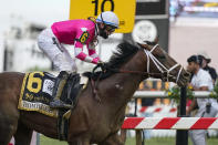 Flavien Prat atop Rombauer reacts as he crosses the finish line to win the Preakness Stakes horse race at Pimlico Race Course, Saturday, May 15, 2021, in Baltimore. (AP Photo/Julio Cortez)