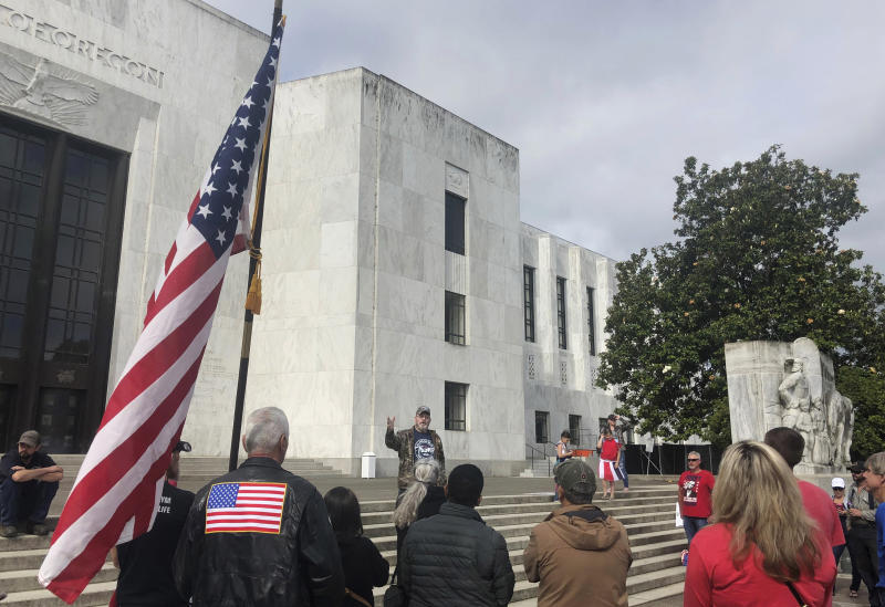 """In this photo taken Sunday, June 23, 2019, a small crowd of local Republicans show their support of a Republican walkout outside the Oregon State Capitol in Salem, Ore. The gathering took place only a day after the Senate President ordered the statehouse to close over a """"possible militia threat,"""" the latest escalation in a Republican walkout over proposed climate policy that has put Democrats' top legislative priorities at risk. (AP Photo/Sarah Zimmerman)"""