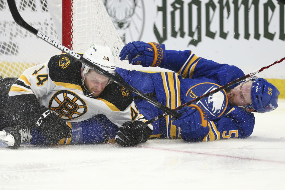 Buffalo Sabres defenseman Rasmus Ristolainen (55) and Boston Bruins defenseman Steven Kampfer (44) crash to the ice during the second period of an NHL hockey game Thursday, April 22, 2021, in Buffalo, N.Y. (AP Photo/Jeffrey T. Barnes)