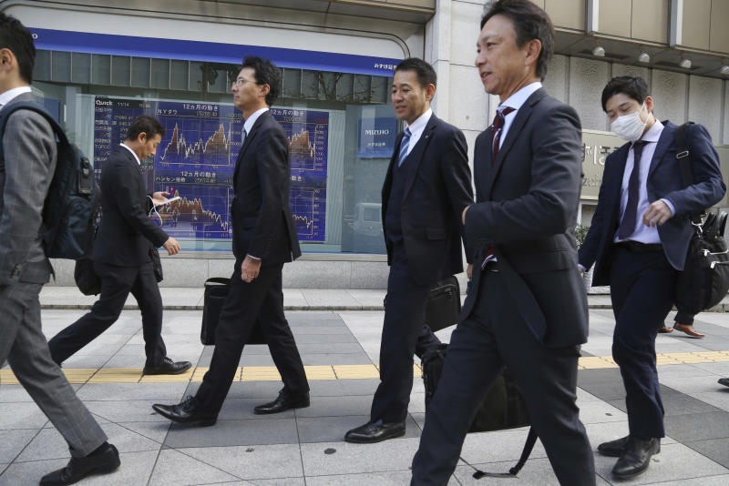 People walk by an electronic stock board of a securities firm in Tokyo, Wednesday, Nov. 14, 2018. Asian shares were mostly lower Wednesday, after the steepest drop in oil prices in more than three years put investors in a selling mood on Wall Street. (AP Photo/Koji Sasahara)