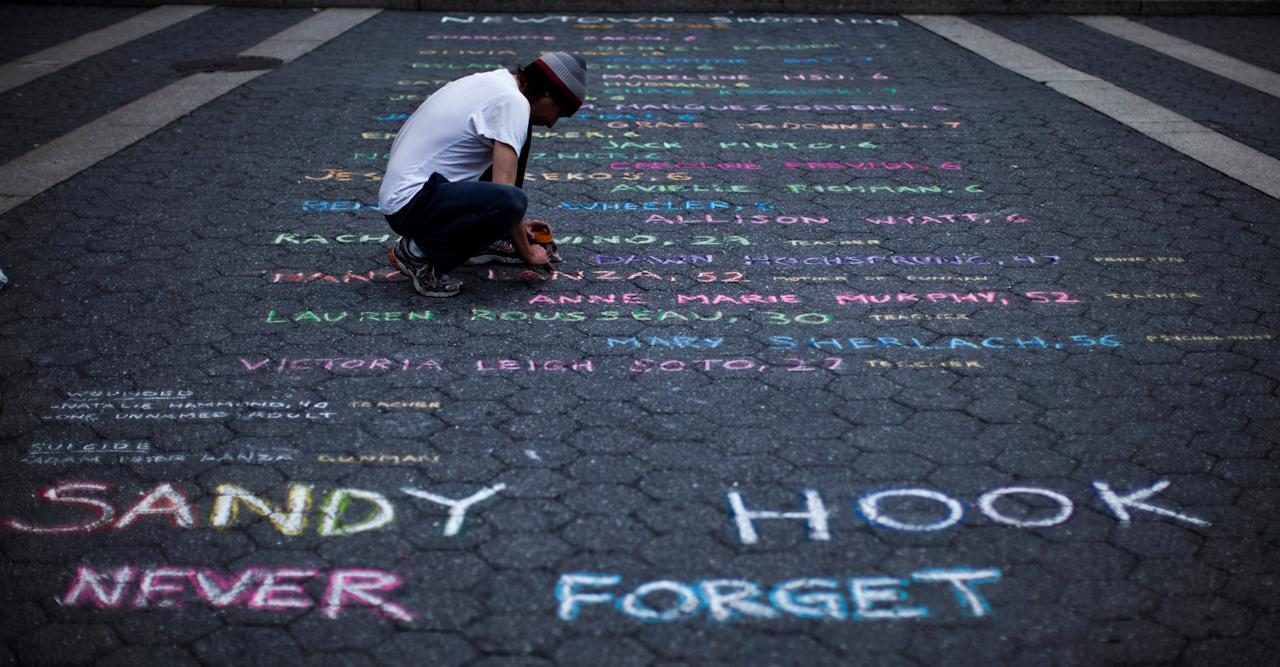 FILE PHOTO: Street artist Mark Panzarino, prepares a memorial as he writes the names of the Sandy Hook Elementary School victims during the six-month anniversary of the massacre, at Union Square in New York, U.S. June 14, 2013.   REUTERS/Eduardo Munoz/File Photo