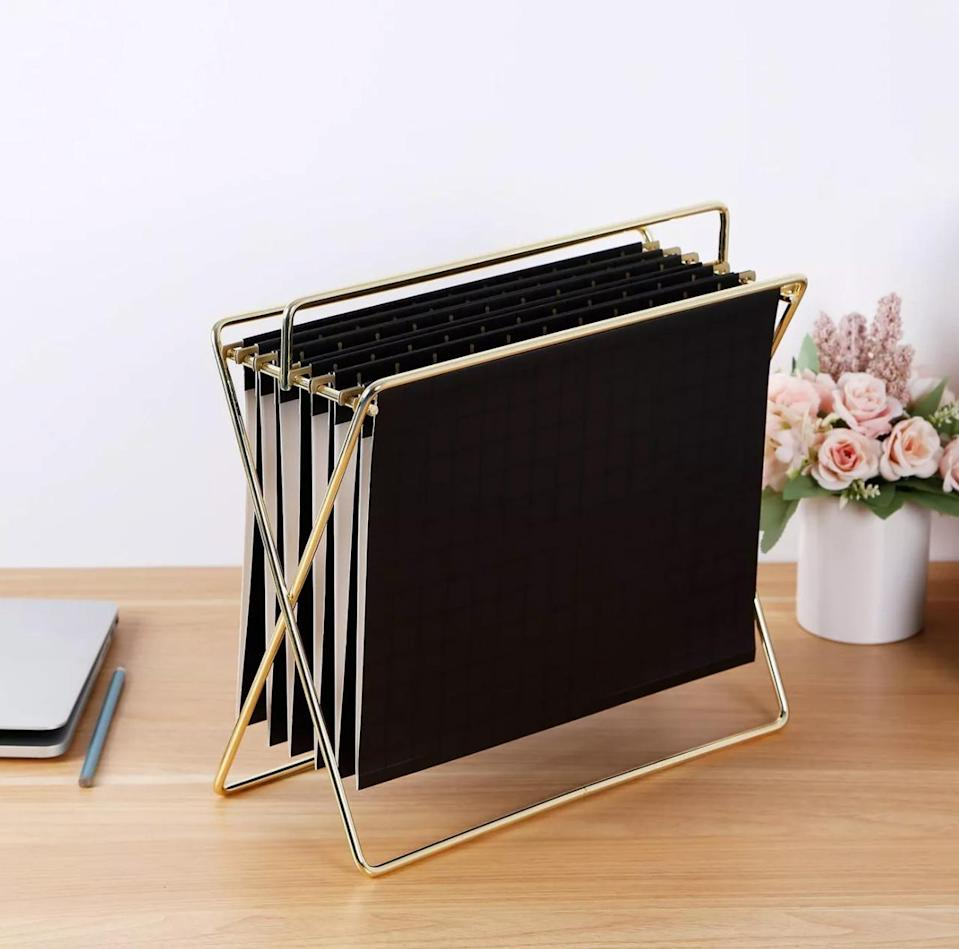 "<p>Even if most of your schoolwork happens online, having a dedicated spot to organizing important papers—like a printout of your syllabus, drafts of the paper you're researching, and tickets to the next home football game—is essential. A minimalist gold-framed holder offers plenty of storage when paired with subtle black folders but won't take up too much valuable desk space.</p> <p><strong><em>Shop Now:</em></strong><em> Project 62 Hanging File Holder with Folders in Gold/Black Grid, $12.99, <a href=""http://goto.target.com/c/249354/81938/2092?subId1=MSL21DormRoomStorageIdeasThatMaketheMostofYourSmallSpacesbamseyStoGal7846410202007I&u=https%3A%2F%2Fwww.target.com%2Fp%2Fhanging-file-holder-with-folders-gold-black-grid-project-62-8482%2F-%2FA-52808782"" rel=""nofollow noopener"" target=""_blank"" data-ylk=""slk:target.com"" class=""link rapid-noclick-resp"">target.com</a>.</em></p>"