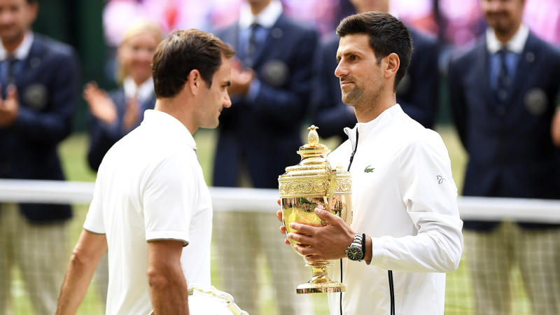 Novak Djokovic carries the Wimbledon trophy and passes Roger Federer.