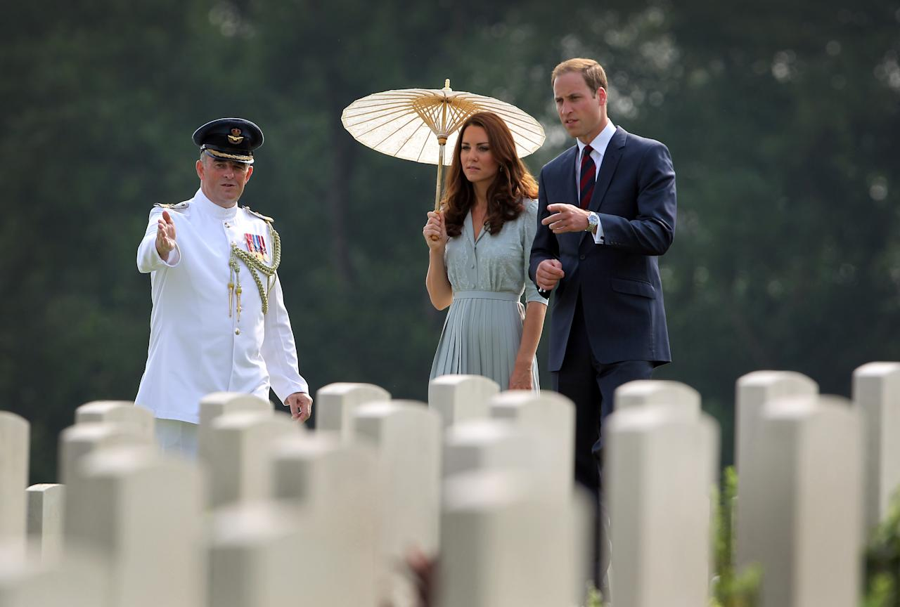 Britain's Prince William, right, and his wife Kate, center, the Duke and the Duchess of Cambridge pay their respects to war dead of both WWI and WWII at the Kranji Commonwealth War Memorial on Thursday Sept. 13, 2012 in Singapore. (AP Photo/Wong Maye-E)
