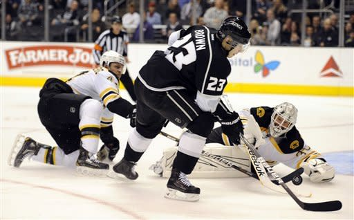Boston Bruins goalie Tim Thomas (30) and defenseman Dennis Seidenberg (44) stop Los Angeles Kings right wing Dustin Brown (23) from scoring in the second period of an NHL hockey game in Los Angeles, Saturday, March 24, 2012. (AP Photo/Lori Shepler)