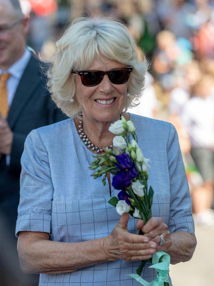 """<p>The Duchess of Cornwall wore a simple blue patterned dress, which she accessorized with a gray pearl necklace, pearl earrings, and brown Ray-Ban sunglasses while on a royal visit with Prince Charles in Wales.<br><br><a class=""""link rapid-noclick-resp"""" href=""""https://go.redirectingat.com?id=74968X1596630&url=https%3A%2F%2Fshop.nordstrom.com%2Fs%2Fray-ban-standard-50mm-folding-wayfarer-sunglasses%2F3236463%3Forigin%3Dkeywordsearch-personalizedsort%26color%3Dbrown%2Bflash&sref=https%3A%2F%2Fwww.goodhousekeeping.com%2Flife%2Fg37187565%2Fcamilla-parker-bowles-fashion-style%2F"""" rel=""""nofollow noopener"""" target=""""_blank"""" data-ylk=""""slk:SHOP NOW"""">SHOP NOW</a> <em>Folding Wayfarer Sunglasses, $153</em></p>"""