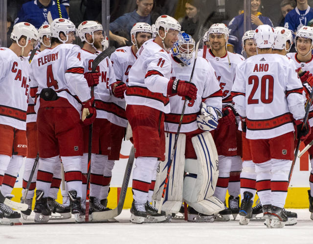 In this Saturday, Feb. 22, 2020 photo, members of the Carolina Hurricanes congratulate emergency goaltender David Ayres after they beat the Toronto Maple Leafs 6-3 in an NHL hockey game in Toronto, Saturday, Feb. 22, 2020. (Frank Gunn/The Canadian Press via AP)