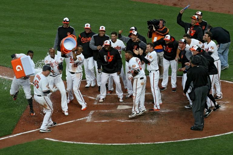Mark Trumbo (No. 45) of the Baltimore Orioles is greeted at home plate after hitting a walk-off home run against the Toronto Blue Jays during the eleventh inning in their opening day game, at Oriole Park in Baltimore, Maryland, on April 3, 2017
