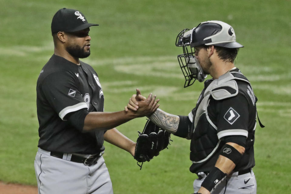 Chicago White Sox relief pitcher Alex Colome, left, and Yasmani Grandal celebrate after the White Sox defeated the Cleveland Indians 4-0 in a baseball game, Wednesday, July 29, 2020, in Cleveland. (AP Photo/Tony Dejak)