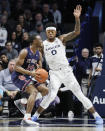 St. John's Mustapha Heron (14) drives against Xavier's Tyrique Jones (0) in the first half of an NCAA college basketball game, Saturday, March 9, 2019, in Cincinnati. (AP Photo/John Minchillo)