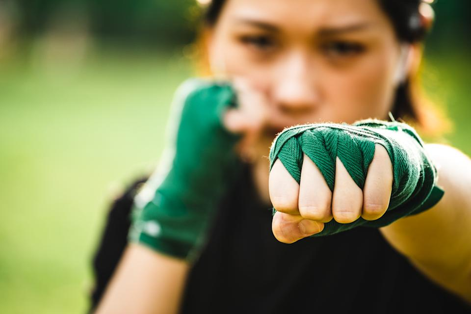 Asian female practicing mixed martial art outdoor