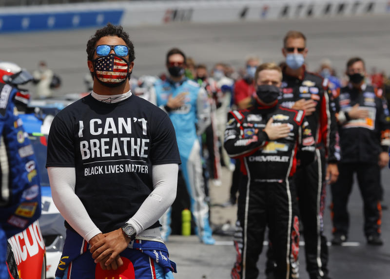 "Bubba Wallace, driver of the #43 McDonald's Chevrolet, wears an ""I Can't Breathe — Black Lives Matter"" T-shirt under his fire suit while standing during the national anthem prior to the NASCAR Cup Series Folds of Honor QuikTrip 500 at Atlanta Motor Speedway on June 07, 2020, in Hampton, Georgia."