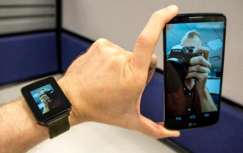 Smartwatch and phone showing an image of the author taking a picture