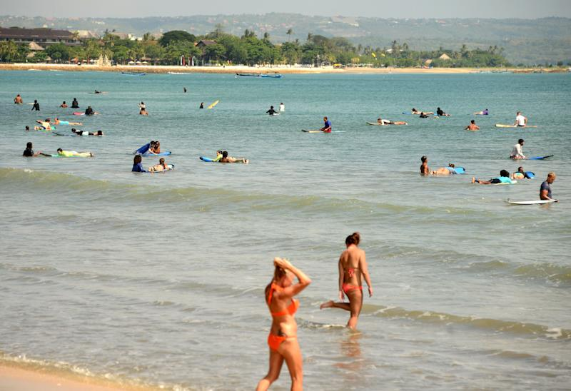 Tourists surf at Kuta beach near Denpasar on Indonesia's resort island of Bali.