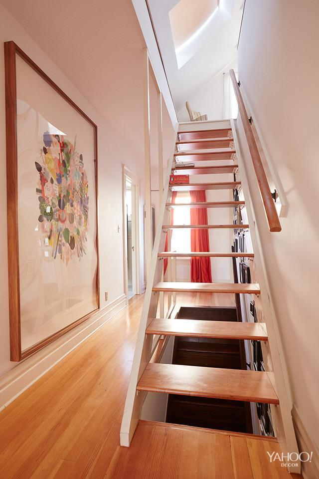 <p>Our upstairs hallway has an open staircase up to the attic room, which really allows the light to come through. A giant piece by the artist Simone Shubuck hangs in the hallway. </p>