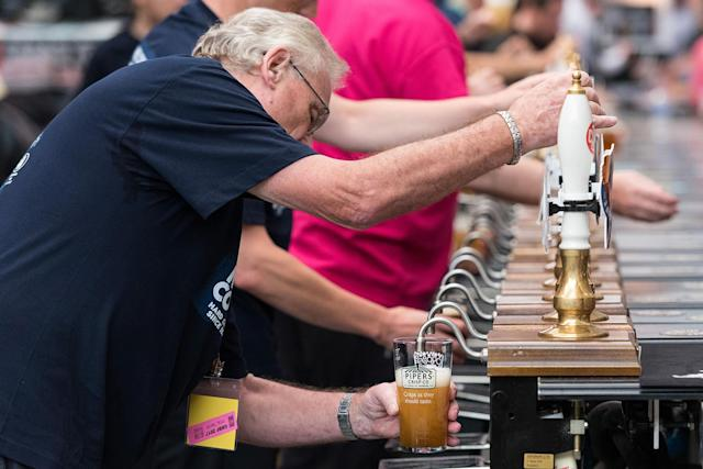 <p>Beer stall staff pulling a pint from a pump to serve hundreds of visitors sample 900 different real ales, craft beers international beers, ciders at the CAMRA Great British Beer Festival in London, Aug. 8, 2017. (Photo: Ray Tang/REX/Shutterstock) </p>
