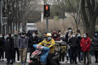 A food delivery worker and office workers wearing face masks to protect themselves from the coronavirus wait to cross a street in Beijing on Thursday, Jan. 14, 2021. The e-commerce workers and delivery people who kept China fed during the pandemic, making their billionaire bosses even richer, are so unhappy with their pay and treatment that one just set himself on fire in protest. (AP Photo/Andy Wong)