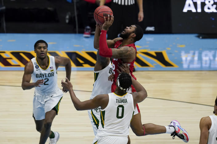 Houston forward Reggie Chaney, top, shoots over Baylor forward Flo Thamba (0) during the second half of a men's Final Four NCAA college basketball tournament semifinal game, Saturday, April 3, 2021, at Lucas Oil Stadium in Indianapolis. (AP Photo/Michael Conroy)