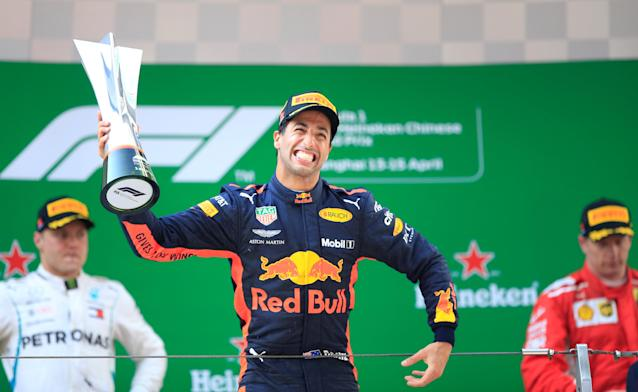 Formula One F1 - Chinese Grand Prix - Shanghai International Circuit, Shanghai, China - April 15, 2018 Red Bull's Daniel Ricciardo celebrates with a trophy on the podium after winning the race as Mercedes' Valtteri Bottas and Ferrari's Kimi Raikkonen look on REUTERS/Aly Song