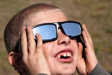 Cooper Jackson tries out his new solar glasses in a designated eclipse viewing area in a campground near Guernsey, Wyoming, U.S., August 20, 2017. REUTERS/Rick Wilking