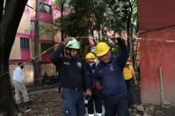Members of Civil Protection and paramedics are seen at an apartment building damaged by an earthquake that struck southern Mexico on Tuesday, in Mexico City