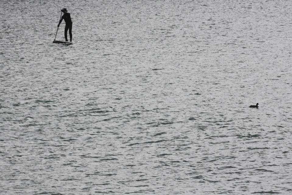 A man enjoys a paddleboard at Enoshima, the venue of sailing competitions at the Tokyo 2020 Olympics, in Fujisawa, near Tokyo, Tuesday, April 6, 2021. Many preparations are still up in the air as organizers try to figure out how to hold the postponed games in the middle of a pandemic. (AP Photo/Koji Sasahara)