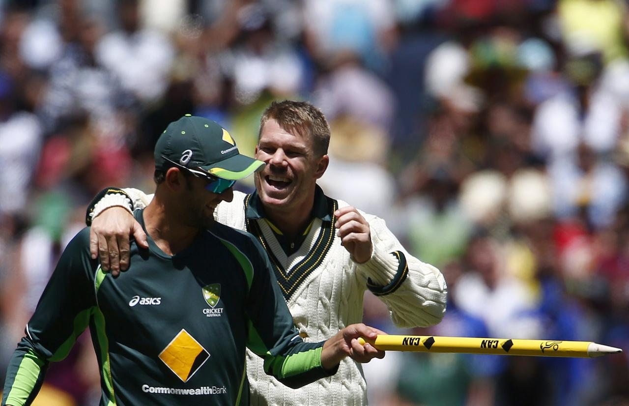 Australia's David Warner (R) celebrates with Nathan Lyon after winning the fourth Ashes cricket test against England at the Melbourne cricket ground December 29, 2013. Australia completed a dominant eight-wicket victory in the fourth Ashes test before tea on day four, swatting away a toothless England at the Melbourne Cricket Ground on Sunday to take a 4-0 lead in the five-test series. REUTERS/David Gray (AUSTRALIA - Tags: SPORT CRICKET)