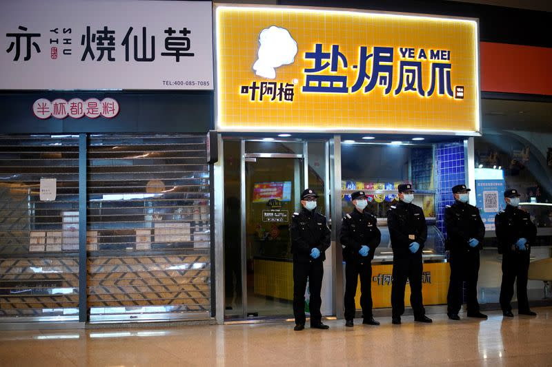 Security personnel wearing face masks stand guard in front of closed shops inside a railway station in Wuhan