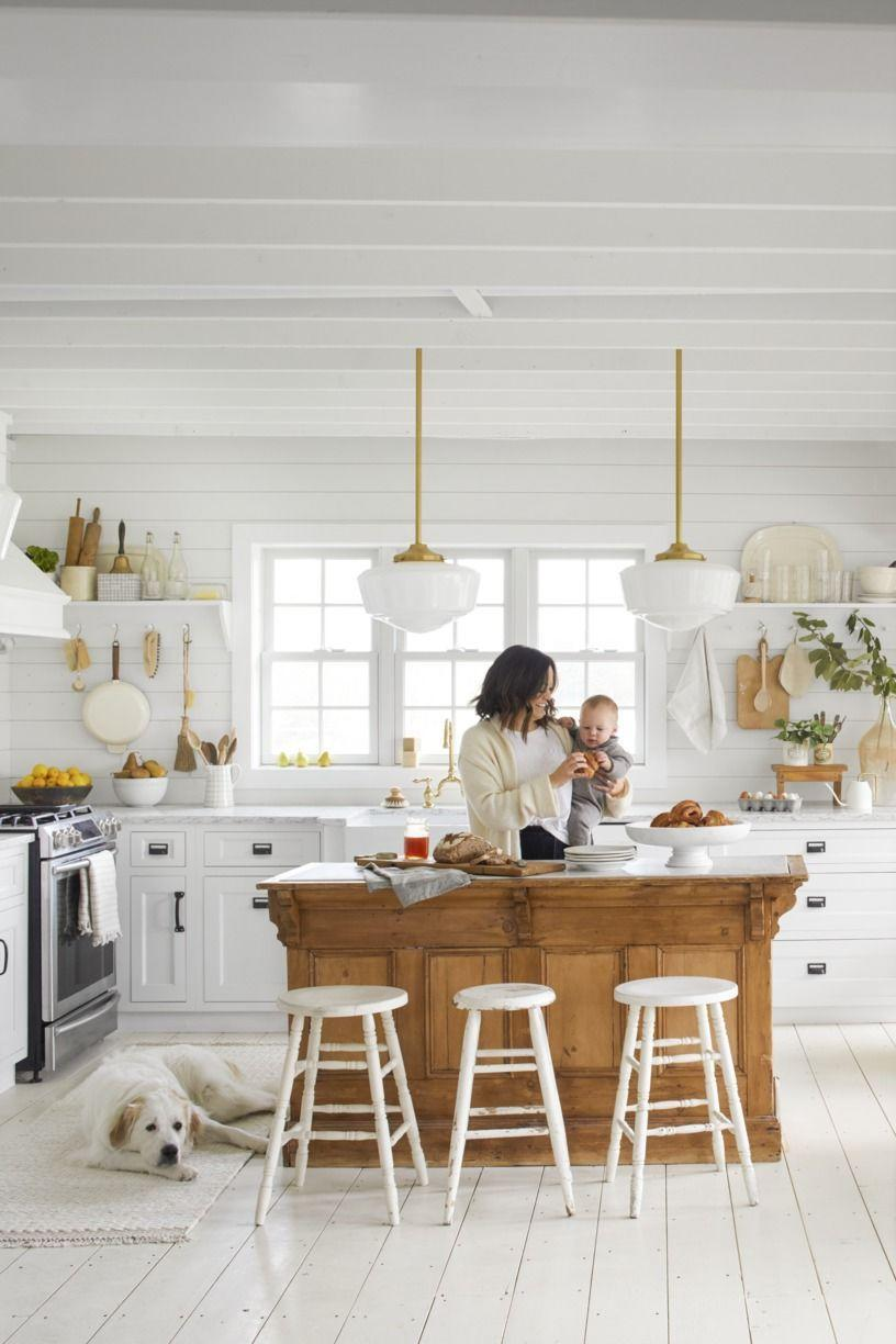 <p>The brass hardware and beautiful antique pine island really warm up this all-white kitchen that feels sophisticated and cozy at the same time. </p>