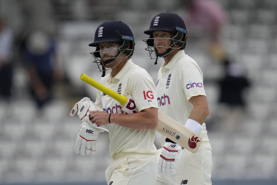 England's Rory Burns and England's Joe Root leave the pitch at the end of play on the second day of the Test match between England and New Zealand at Lord's cricket ground in London, Thursday, June 3, 2021. (AP Photo/Kirsty Wigglesworth)