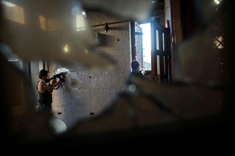 Rebel fighters from the Islamic Front, an umbrella of Islamist rebel groups in Syria, fire their weapons during clashes with government forces in the old city of Aleppo on July 21, 2014