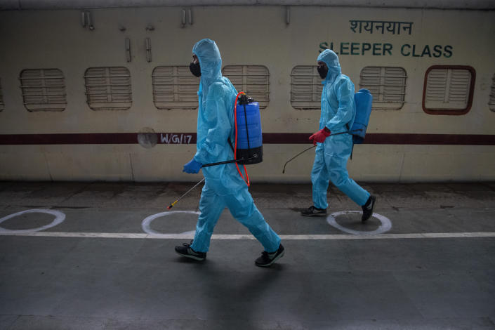 Health workers in personal protective equipment sanitize a train prepared as COVID-19 care centre in the wake of spike in the number of positive coronavirus cases, at a railway station in Gauhati, India, Thursday, May 6, 2021. Infections in India hit another grim daily record on Thursday as demand for medical oxygen jumped seven-fold and the government denied reports that it was slow in distributing life-saving supplies from abroad. (AP Photo/Anupam Nath)