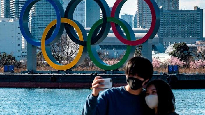A couple take a selfie in front of the Olympic rings on display at the Odaiba waterfront in Tokyo