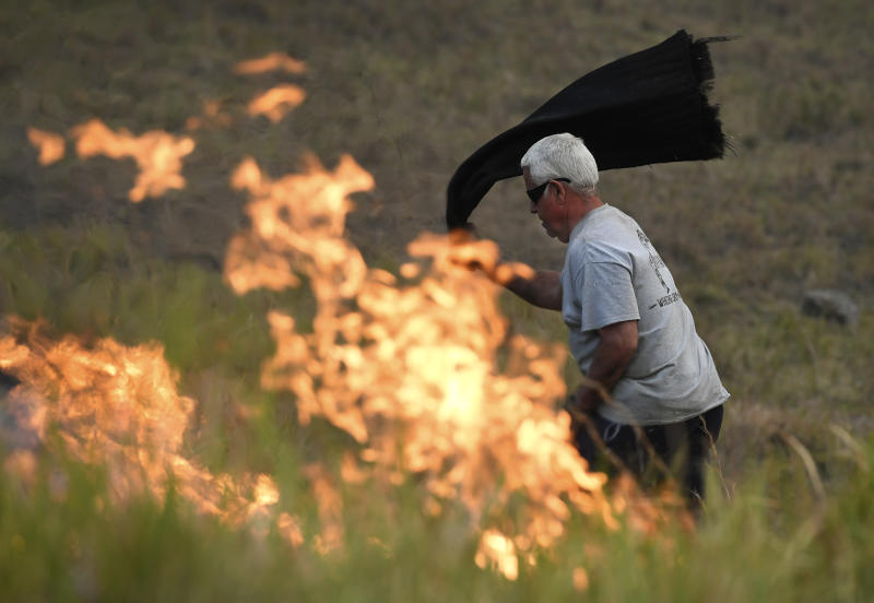 A man uses a wet towel to help put out flames as they encroach on farmland near the town of Taree, some 350km north of Sydney.