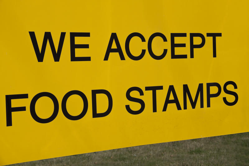 Gold sign with black lettering reads We Accept Food Stamps