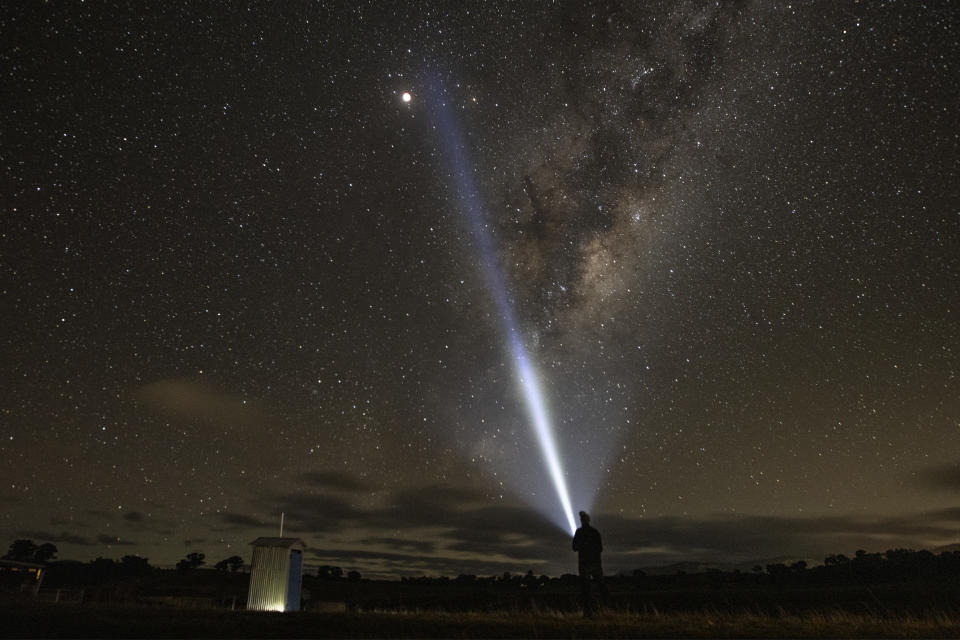 RYLSTONE, AUSTRALIA - MAY 26: A man looks towards the supermoon and the milky way on May 26, 2021 in Rylstone, Australia. It is the first total lunar eclipse in more than two years, which coincides with a supermoon.  A super moon is a name given to a full (or new) moon that occurs when the moon is in perigee - or closest to the earth - and it is the moon's proximity to earth that results in its brighter and bigger appearance. (Photo by Mark Evans/Getty Images)