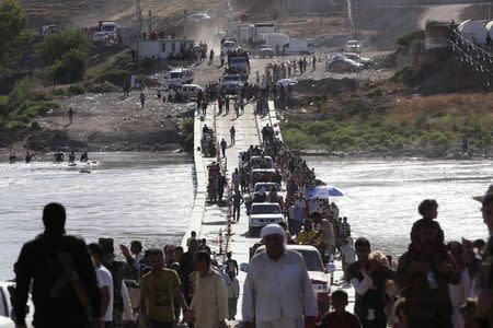 Displaced people from the minority Yazidi sect, fleeing the violence in the Iraqi town of Sinjar, re-enter Iraq from Syria at the Iraqi-Syrian border crossing in Fishkhabour, Dohuk province, August 10, 2014. REUTERS/Ari Jalal